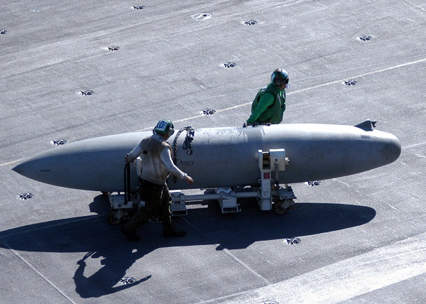 A 330 US gallons (1,200 L) Sargent Fletcher drop tank being moved across the flight deck of an Aircraft carrier.